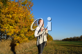 Girl on a background of yellow leaves of autumn trees. Autumn photo session