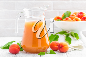Apricot juice and fresh fruits with leaves on white wooden table