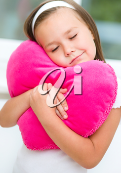Little girl closed her eyes dreaming, holding a pillow