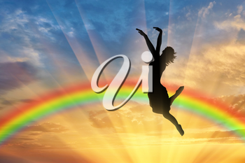 Rainbow and happiness. Happy woman jumping at sunset near the rainbow
