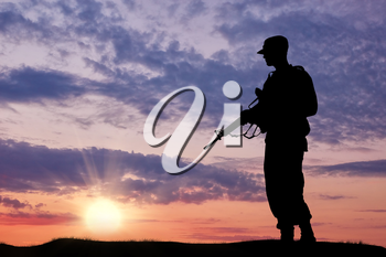 Silhouette of soldier with a gun on a background of sunset