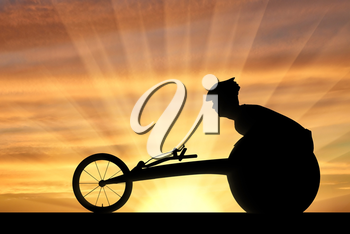 Silhouette of sportsman disabled in a racing wheelchair. The concept of disabled sportsmen