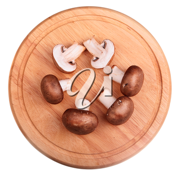 Brown champignon mushroom isolated on wooden board