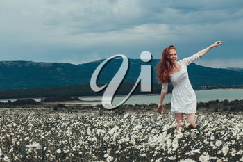Beautiful young girl with curly red hair in chamomile field