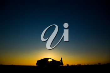 Silhouette of sedan car with girl on the background of beautiful sunset