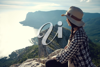 woman traveler with backpack holding hat and looking at amazing mountains and forest, wanderlust travel concept, space for text, atmospheric epic moment