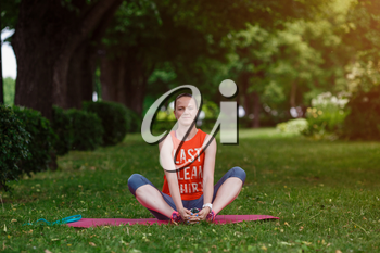 Young beautiful woman meditates on a summer day in the park. Idea and concept of calm in a busy city and a healthy lifestyle, stretching and preparing for a run in the park