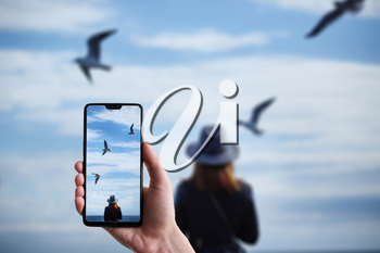 A man makes a photo on a smartphone, Girl looking at the calm sea on the with wind in her hair and seagulls on the background. Autumn in the Hat