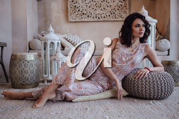 Charming model posing in her vacation to Morocco in her riad in Marrakech. Beautiful arab woman resting after walking in the desert.