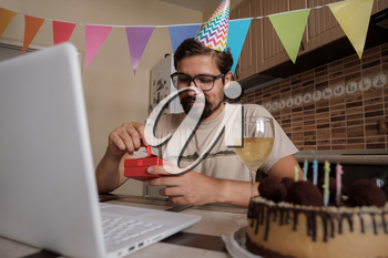 Man celebrating birthday online in quarantine time. Coronavirus outbreak 2020. The guy opens the box and is very happy with the gift. Communicating with friends remotely