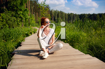 ginger charming woman young beautiful forest green. Caucasian girl relaxing and enjoying life on nature outdoors.