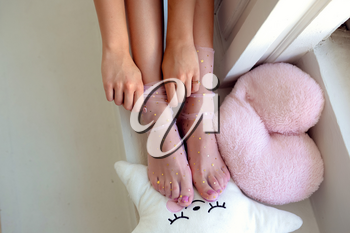 Beautiful groomed woman's feet in the socks with stars. Care about nails and clean, soft, smooth body skin. Pedicure and manicure beauty salon.