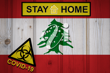 Flag of the Lebanon in original proportions. Quarantine and isolation - Stay at home. flag with biohazard symbol and inscription COVID-19.