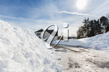 Piles of snow after the driveway to a modern single family house has been cleared after blizzard and snow drifts