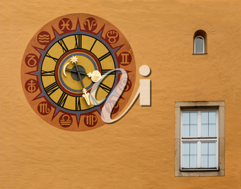 Ancient clock face on wall in the medieval town of Regensburg, Bavaria, Germany