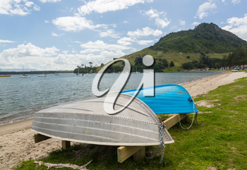 Bay and harbour at Tauranga with two rowing boats on the sandy beach by calm water in front of the Mount