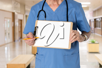 Senior male caucasian doctor with stethoscope in medical scrubs and holding clipboard for message with pencil for emphasis