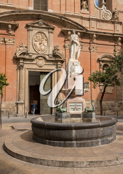 Statue and fountain outside Church of Santo Tomas in old city of Valencia in Spain
