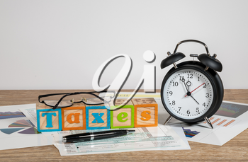 Alarm clock approaching midnight on tax day and taxation forms not completed
