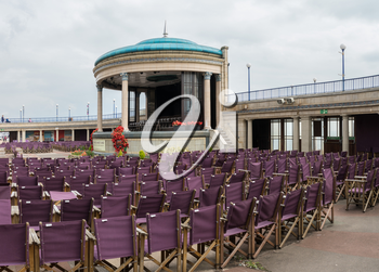 EASTBOURNE, UK - SEPTEMBER 19, 2016: Empty folding seats at seaside theater stage on promenade at Eastbourne, UK