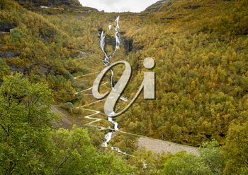 Multiple hairpin bends and zigzags as road climbs mountain  from the train between Flam and Myrdal in Norway