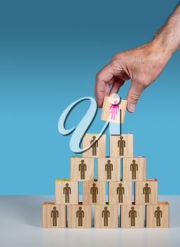 Older mans hand placing a woman CEO or leader at the top of an organization chart made from blocks