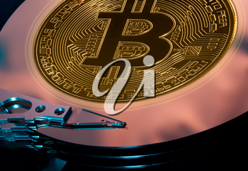Bitcoin superimposed on the discs of a hard drive storage to illustrate bitcoin mining
