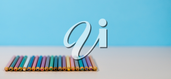 Set of colourful drawing pencils laid side by side on white desk for back to school concept with copy space