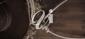 Classical cowboy hat and lasso lie on old boards on the ranch