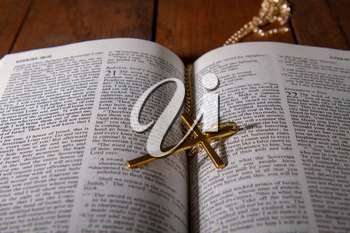 Open holy bible close up and a small metal cross on a chain