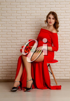 Beautiful young girl six months pregnant in a bright red dress with a bouquet of tulips sitting on a chair against a brick wall