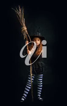 little witch girl in traditional Halloween dress and pointed hat is standing with a wooden whisk on a dark background