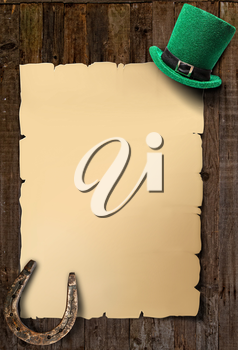 Poster for St. Patrick's Day empty sheet of paper, green leprechaun hat and horseshoe on an old wooden background