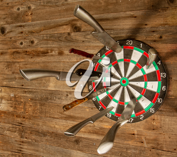 several different steel kitchen knife stuck in a dartboard