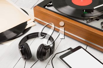 Vintage turntable, smartphone and headphones on the wooden background