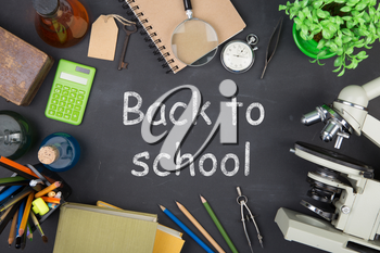 Education concept - books, microscope and Back to school inscription on the blackboard