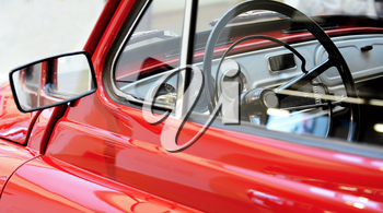 Side view through a window to interior of classic vintage red car.