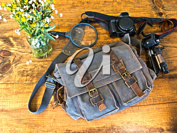 Bleu Satchel With Camera, Tripod and Magnefying Glass Sitting on Wooden Table