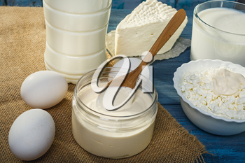 Farm dairy products and a spoon of sour cream on a blue wooden table