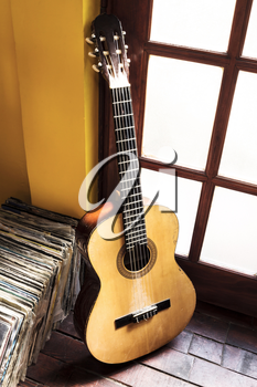 Old dusty guitar and records on the wooden flor