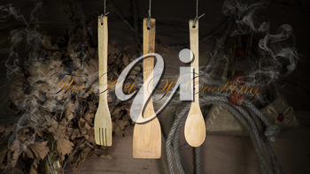 Kitchen Utensils Hanging On A Rope Against Rustic Wooden Background
