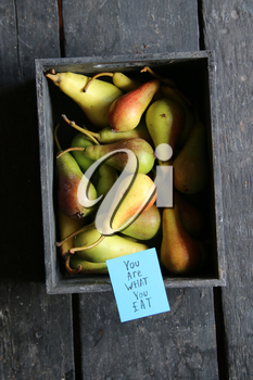 You are what to eat tag and Raw Organic Pears in wooden box on table on old vintage table.