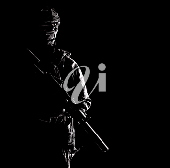 Portrait of modern infantry soldier, special operations forces rifleman, police tactical group fighter in helmet and mask armed with silenced service rifle, low key with hard side light studio shoot