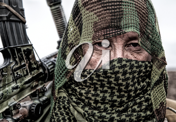 Army marksman, airsoft player in camouflage uniform and load carrier, masking cape on head, armed service rifle with optical sight, hiding face with shemagh, standing on field, looking into distance