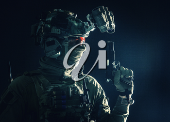 Side view portrait of army soldier, modern combatant, special forces fighter in helmet, night-vision device, radio headset, hiding identity behind mask, armed service pistol, low key studio shoot
