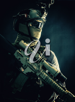 Shoulder portrait of army elite troops sniper, anti-terrorist tactical team marksman wearing helmet with thermal imager, hiding face behind mask, armed rifle with optical scope, studio shoot on black