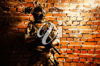 Special operations forces soldier, counter terrorism assault team fighter with night vision device on helmet and service rifle, low key indoor shot brick wall