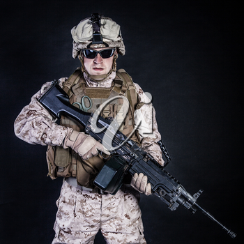 US marine with his assault rifle on black background