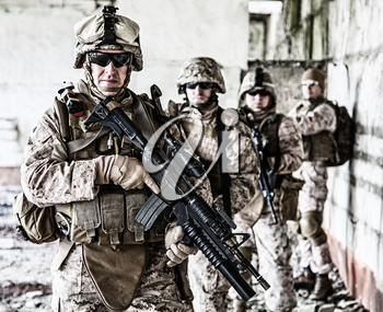Squad of US marines in ruined building