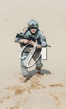 United states airborne infantry man with arms, camo uniforms dress. Combat helmet, knee pads protection wearing, tired and exhausted. moving desert high angle top view